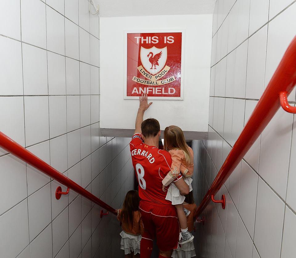 """Com as filhas ao colo, Gerrard toca pela última vez enquanto capitão do Liverpool na mítica placa dos balneários de Anfield Road"""" Fonte: Facebook do Liverpool"""
