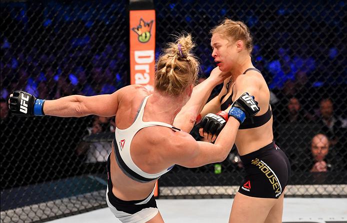 Holly Holm (branco) desfere o pontapé que termina o reinado e onda invicta de Rousey (preto) Fonte: UFC